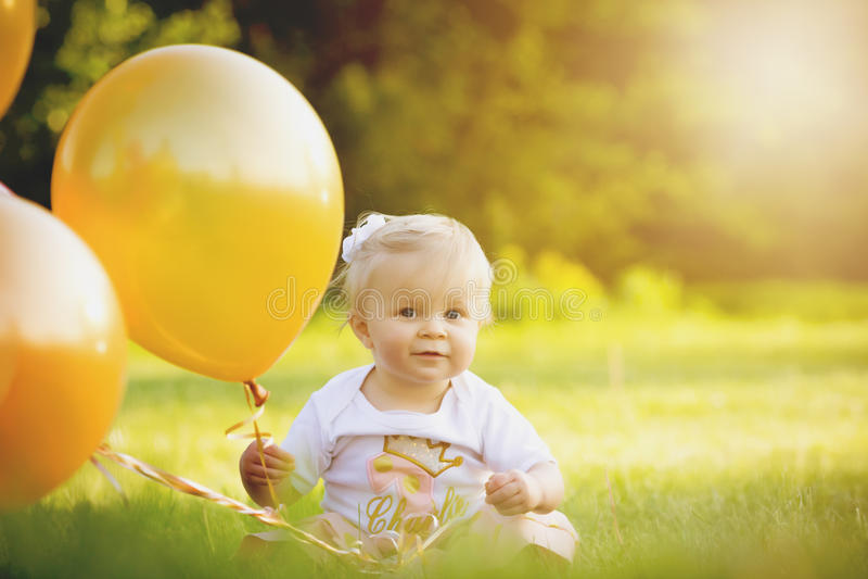 愉快的矮小的白肤金发的白种人女孩外面与气球 库存图片