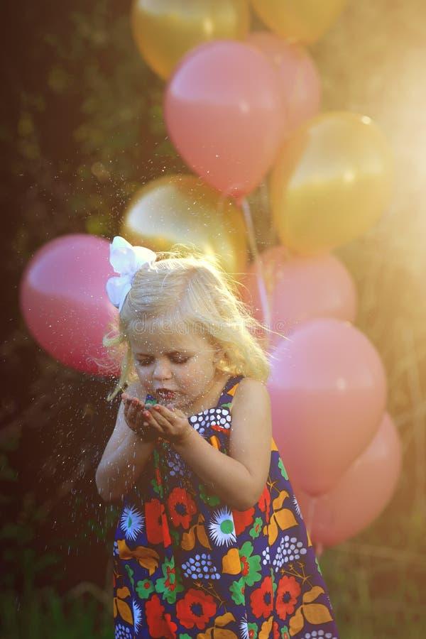 愉快的矮小的白肤金发的白种人女孩外面与气球 图库摄影