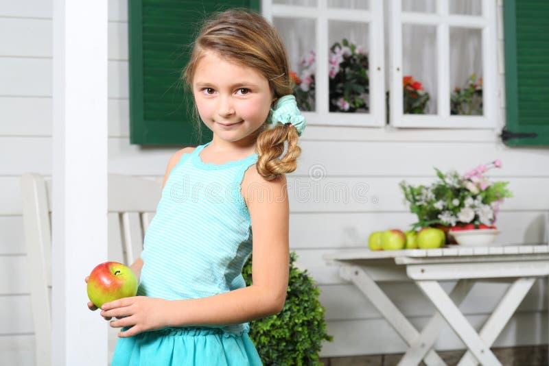 愉快的矮小的美丽的女孩在白色桌附近拿着苹果 库存照片