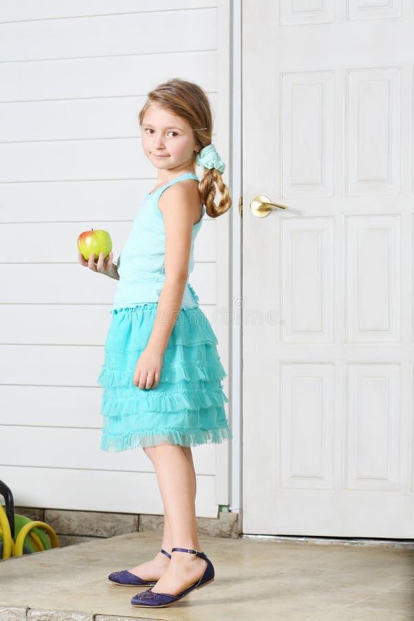 愉快的矮小的美丽的女孩拿着苹果并且站立白色门 库存图片