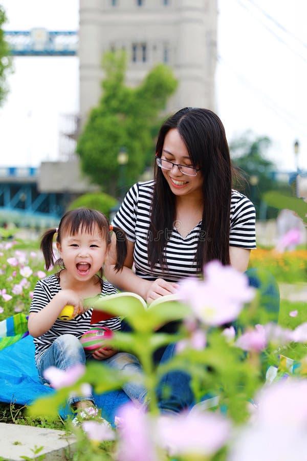 愉快的矮小的逗人喜爱的女婴微笑和笑读与母亲的书,妈妈讲故事给他的夏天公园愉快的家庭的女儿 库存照片
