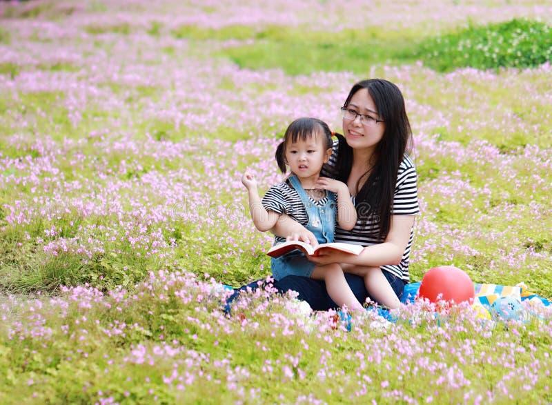 愉快的矮小的逗人喜爱的女婴微笑和笑读与母亲的书,妈妈讲故事给他的夏天公园愉快的家庭的女儿 库存图片