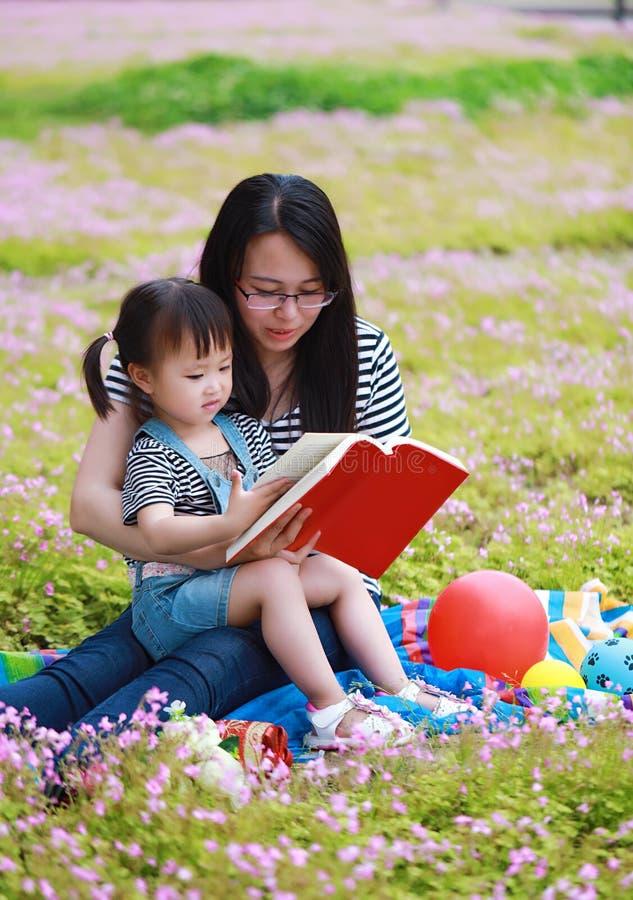 愉快的矮小的逗人喜爱的女婴微笑和读的书与母亲,妈妈讲故事给他的女儿夏天公园愉快的家庭的 免版税库存照片