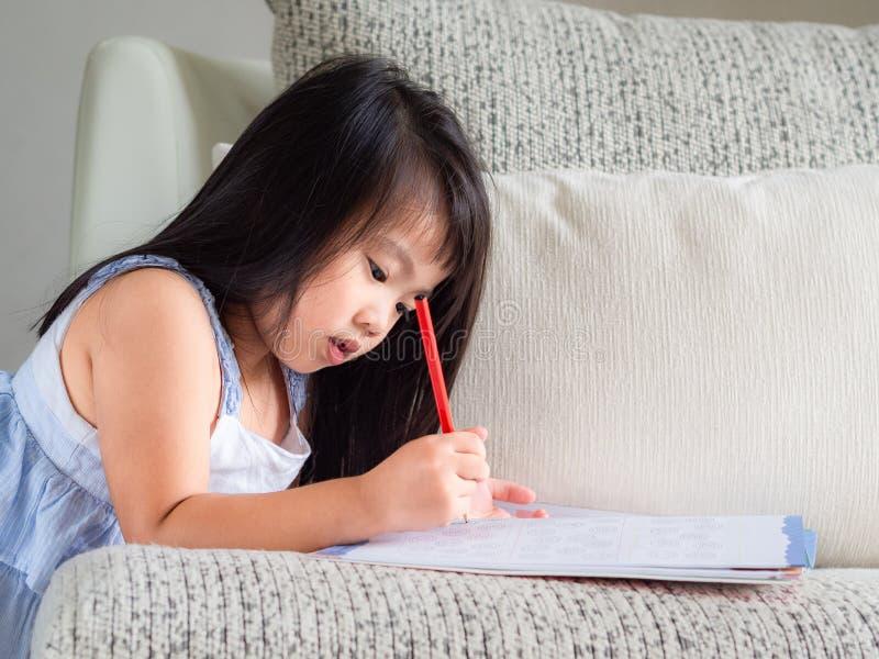 愉快的矮小的逗人喜爱的女孩在Th写着与红色铅笔的书 免版税库存照片