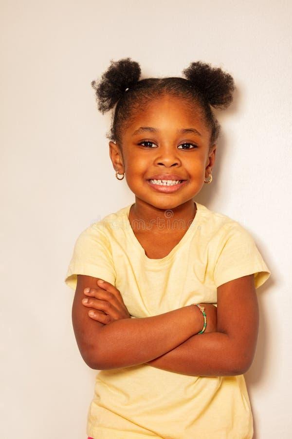 愉快的矮小的黑女孩微笑接近的画象  免版税图库摄影