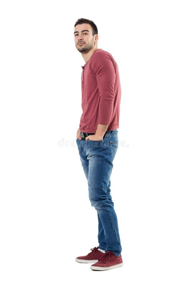 愉快的确信的人佩带的牛仔裤和红色衬衣侧视图用手在口袋 图库摄影