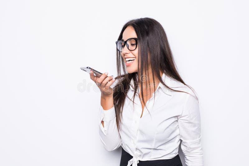 愉快的确信的女实业家谈话在在白色背景隔绝的扬声麦克风的流动手机 免版税库存图片