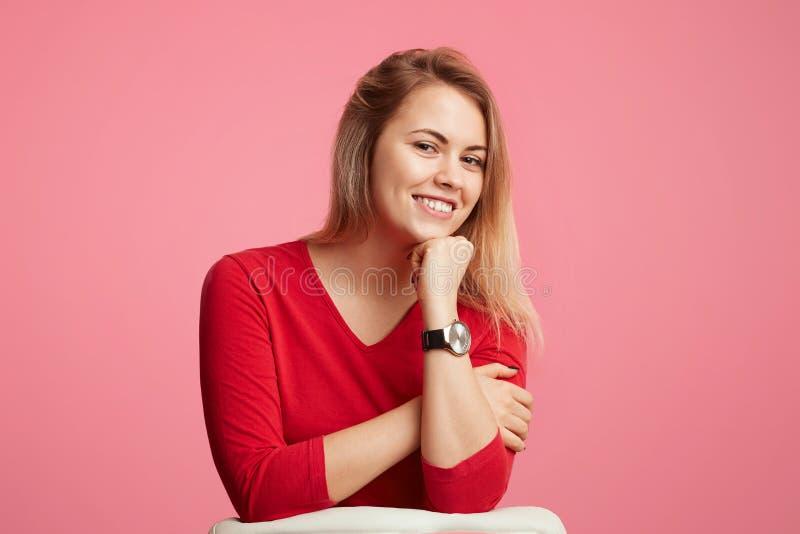 愉快的确信的白肤金发的可爱的妇女保留手在下巴下,有光亮的微笑,穿红色毛线衣,被隔绝在桃红色背景 免版税库存图片