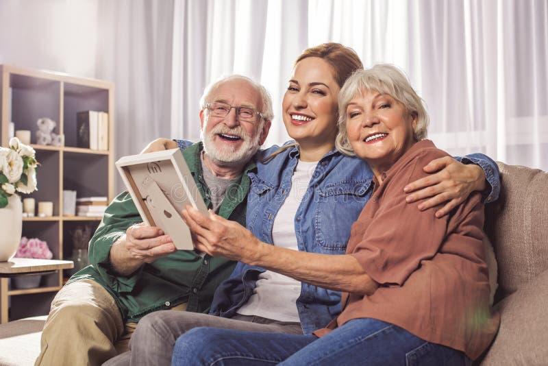 愉快的祖父母和女性举行的照片 库存照片