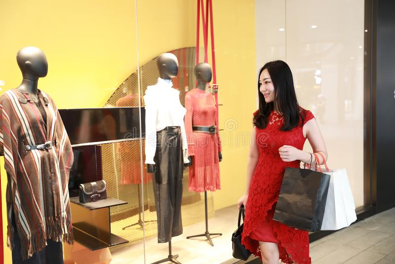 愉快的秀丽亚洲中国现代时髦的女人女孩购物卡片和袋子在购物中心商店偶然买家由窗口走 图库摄影