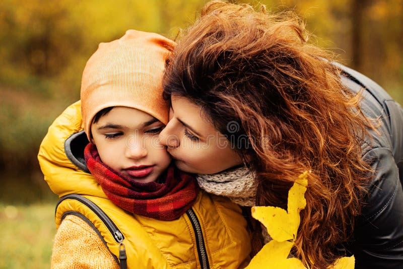 愉快的秋天家庭 儿童爱恋的母亲 免版税库存图片