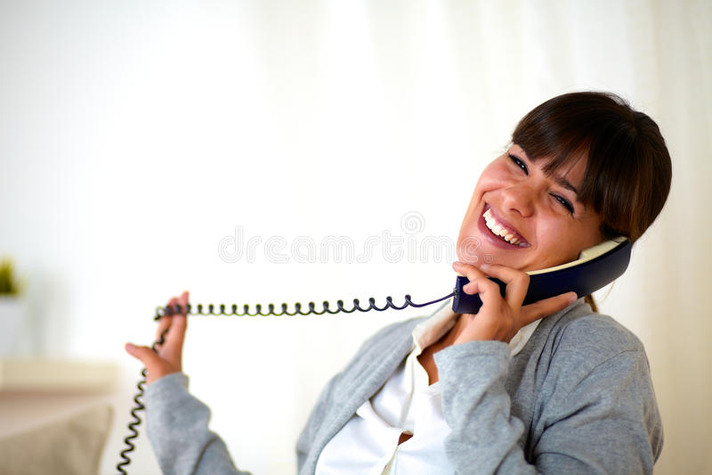 愉快的笑的妇女在家交谈在电话 图库摄影