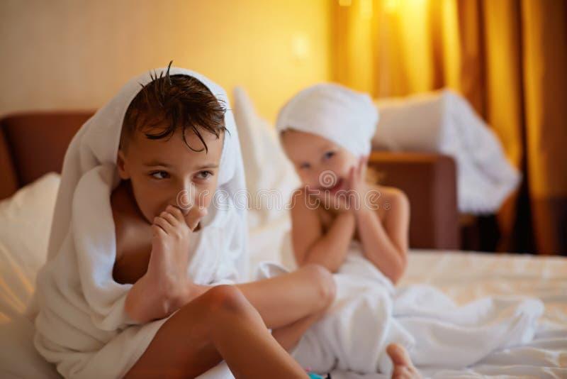 愉快的笑的孩子、男孩和女孩软的浴巾的在浴以后在白色床上使用与白色枕头在晴朗的卧室 孩子 图库摄影