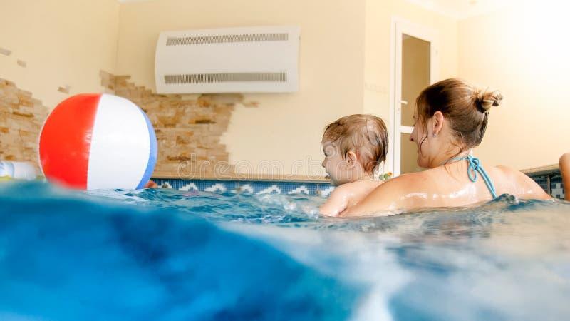 愉快的笑的小孩男孩画象有使用与在游泳场的五颜六色的可膨胀的海滩球的年轻母亲的在 库存照片