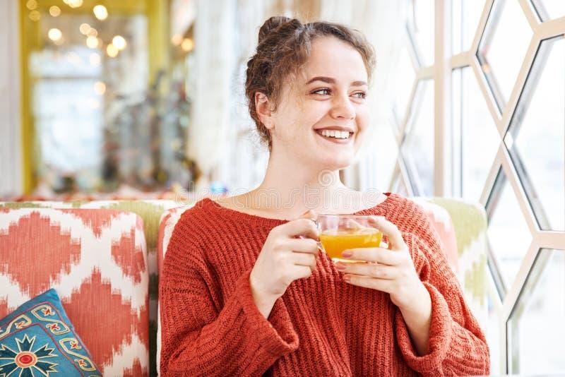 愉快的笑的年轻红头发人妇女吃早餐在一个咖啡馆清早与杯 免版税库存图片