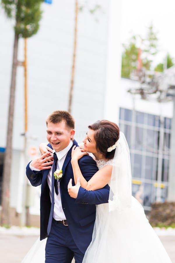 愉快的笑的新娘和新郎画象在街道上晴天 库存照片