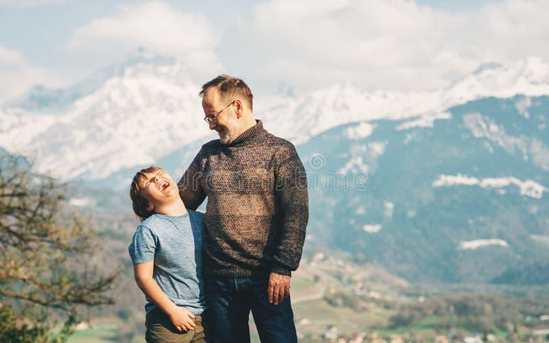 愉快的笑的步行在山的父亲和儿子 库存照片