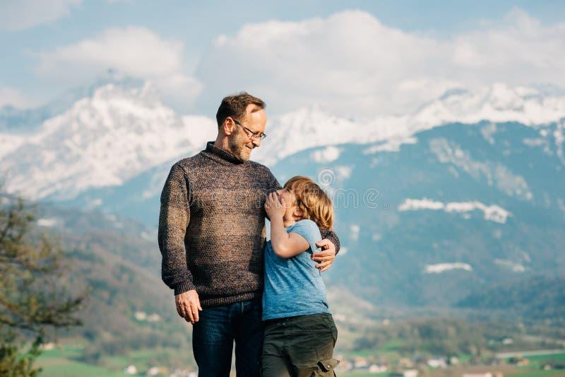 愉快的笑的步行在山的父亲和儿子 库存图片