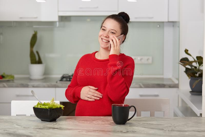 愉快的笑的深色的妇女照片坐在厨房里和讲话通过智能手机与朋友或huband,女性等待 库存图片