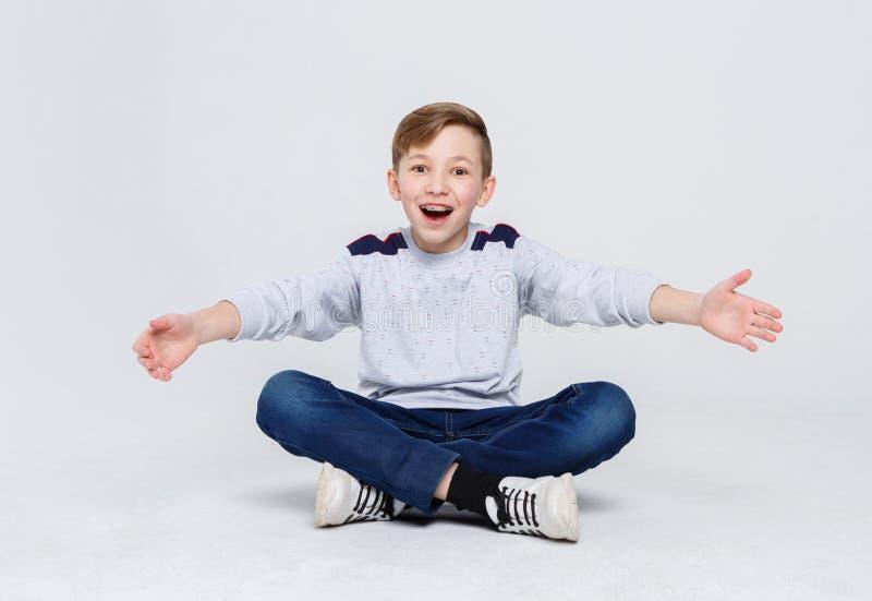 愉快的笑的男孩坐演播室地板 免版税库存图片
