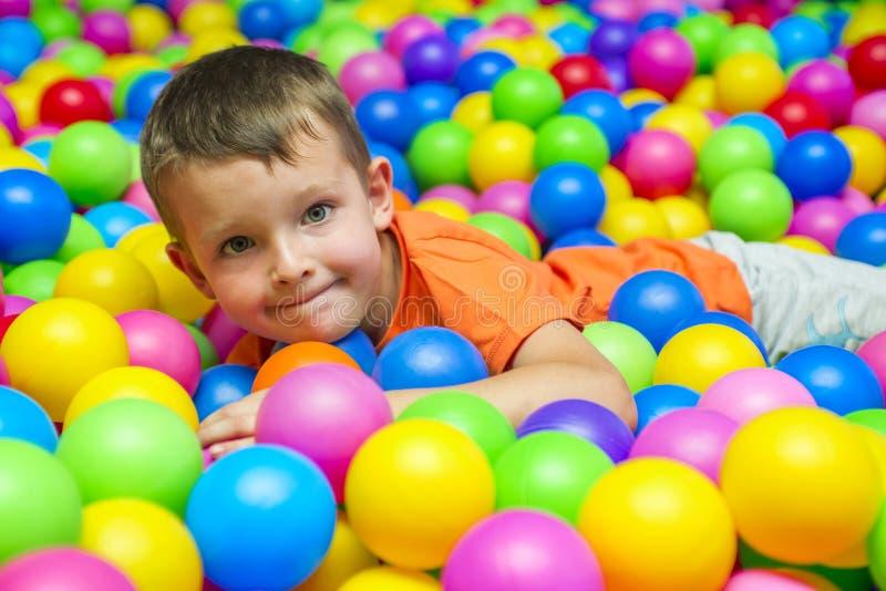 愉快的笑的男孩获得乐趣在球坑在孩子游乐场和演奏中心 使用与五颜六色的球的孩子在操场 免版税库存照片