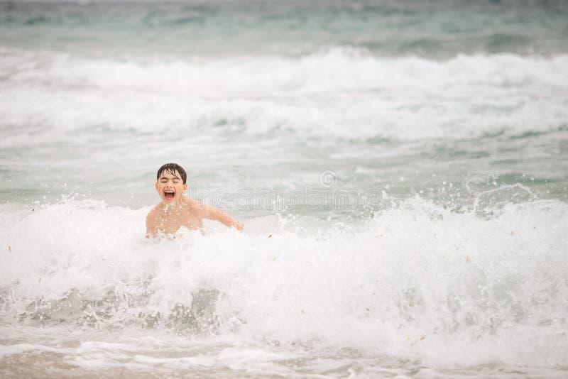 愉快的笑的男孩跳过海浪潮 免版税图库摄影