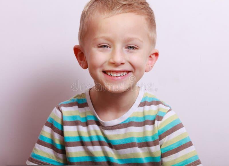 愉快的笑的白肤金发的男孩儿童孩子画象在桌上 免版税库存图片