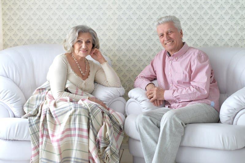 愉快的笑的资深夫妇在家 免版税库存照片