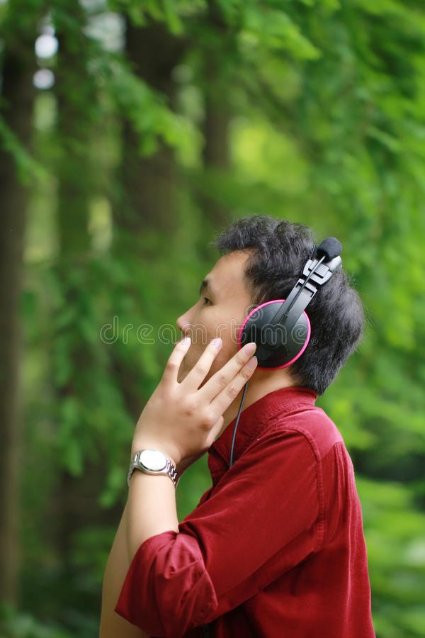 愉快的粗心大意的自由的亚裔中国人听到音乐并且佩带一副黑红色耳机 图库摄影