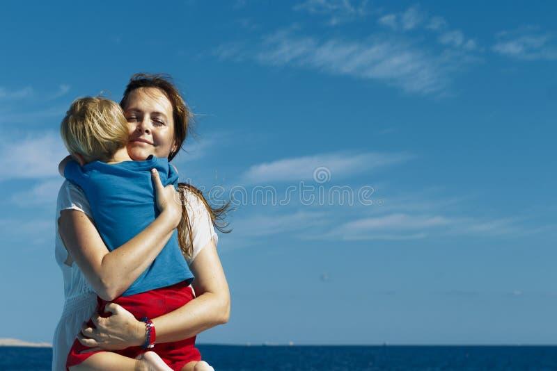 愉快的系列 年轻母亲拿着男婴反对天空蔚蓝背景在好日子 画象妈妈和一点儿子的 免版税库存照片