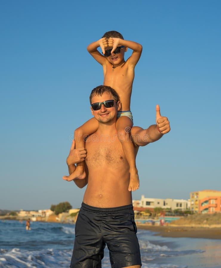 愉快的系列 年轻美丽的父亲和他微笑的儿子获得的男婴在海滩的乐趣海,海洋,显示赞许和 库存照片