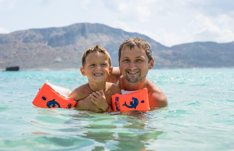 愉快的系列 年轻美丽的父亲和他微笑的儿子获得的男婴在海滩的乐趣海,海洋 正面人的emotio 免版税图库摄影