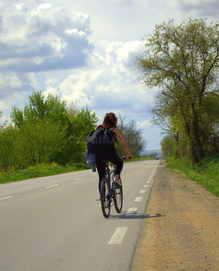 愉快的红色头发骑自行车的人妇女 免版税库存照片