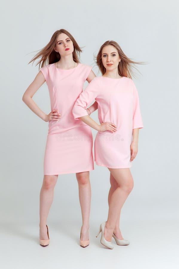 愉快的美丽的两名妇女全长画象摆在演播室的桃红色礼服的隔绝在白色背景 库存照片