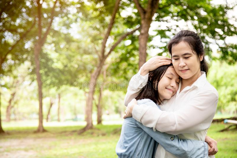 愉快的美丽的亚裔妇女和逗人喜爱的儿童女孩有拥抱和微笑的在夏天,母亲爱有她的小女儿的 免版税图库摄影
