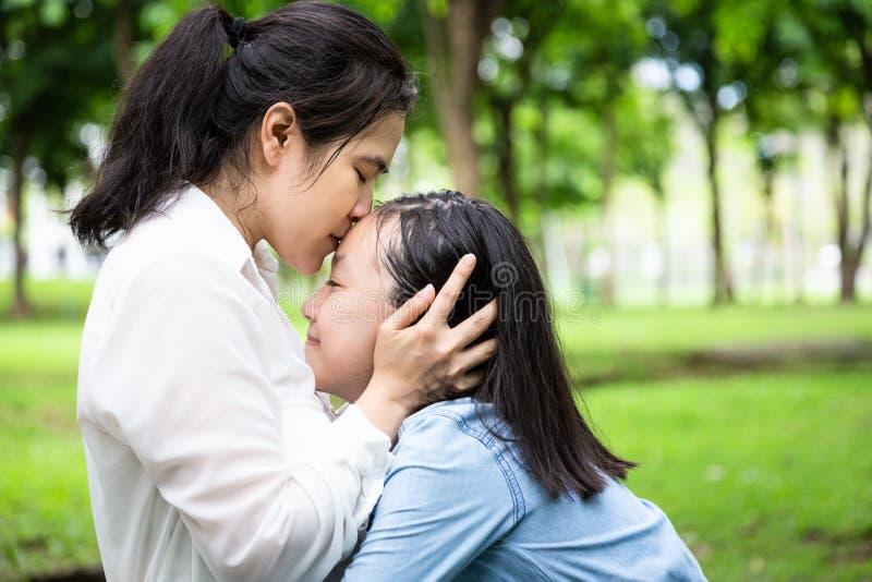 愉快的美丽的亚裔妇女和逗人喜爱的儿童女孩有拥抱,亲吻和微笑的在夏天,母亲爱有她小的 图库摄影