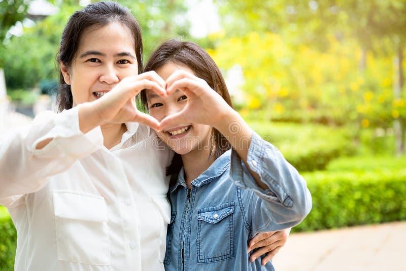 愉快的美丽的亚裔妇女和逗人喜爱的形成心脏用他们的手的儿童女孩,当拥抱和微笑在庭院,爱里时 库存照片