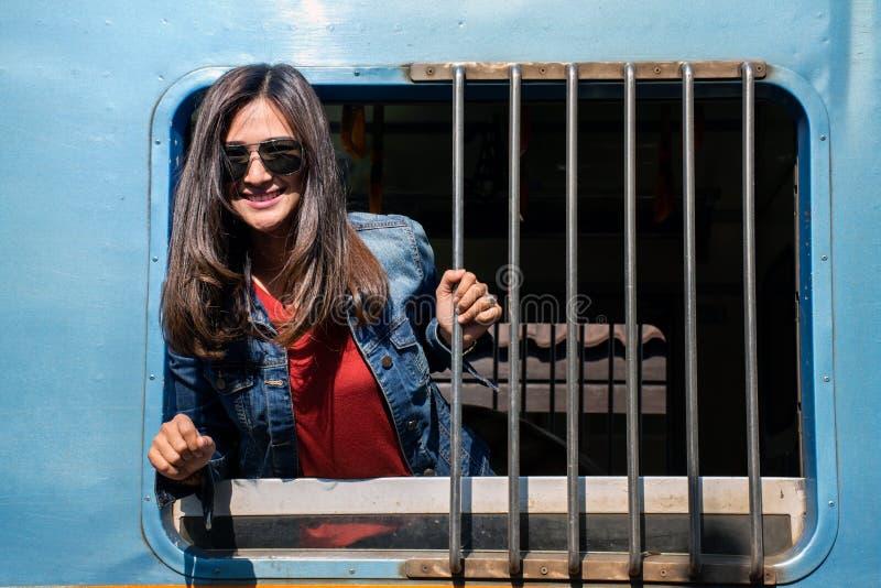 愉快的美丽的亚裔旅行乘火车的妇女佩带的太阳镜看从窗口 免版税库存照片