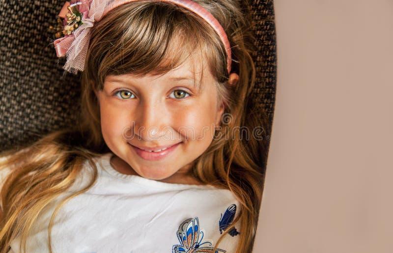 愉快的美丽的女孩 咧嘴在与微笑的照相机的可爱的白肤金发的女孩 E 免版税库存照片