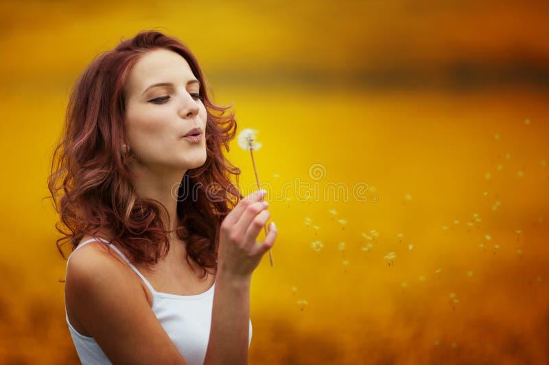 愉快的美丽的妇女吹的蒲公英 免版税库存照片