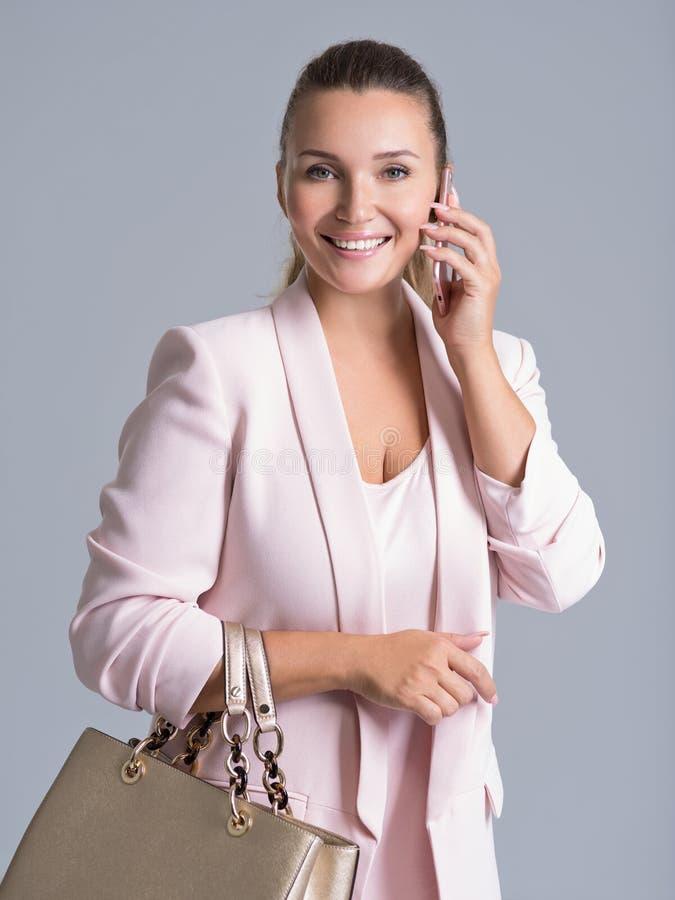愉快的美丽的妇女拿着提包和机动性 免版税库存照片