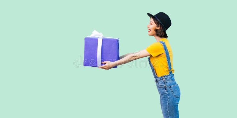 愉快的美丽的少女侧视图行家穿戴的在牛仔布总体和黑帽会议身分和给您大重的礼物盒 库存图片