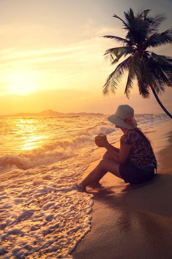 愉快的美丽的少妇穿戴草帽剪影侧视图-坐海滩在夏天在日落时间 库存图片