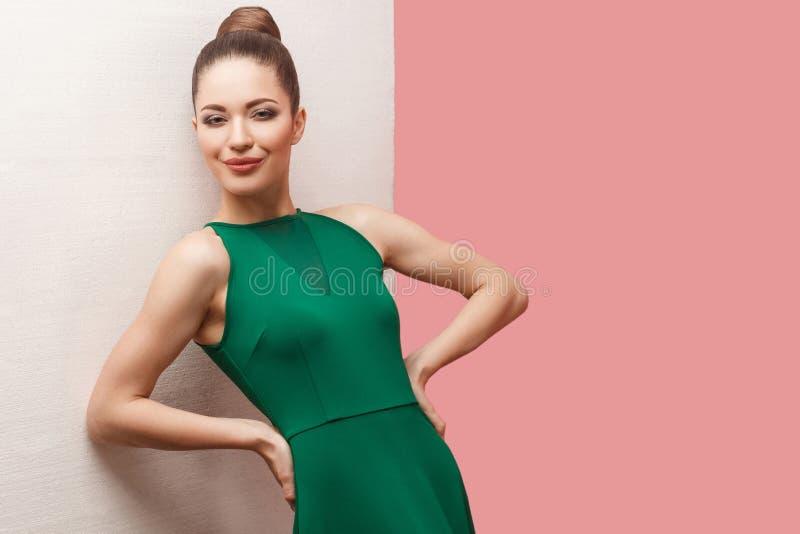 愉快的美丽的年轻女人画象有小圆面包发型和构成在绿色礼服身分用手在腰部和看的 免版税图库摄影
