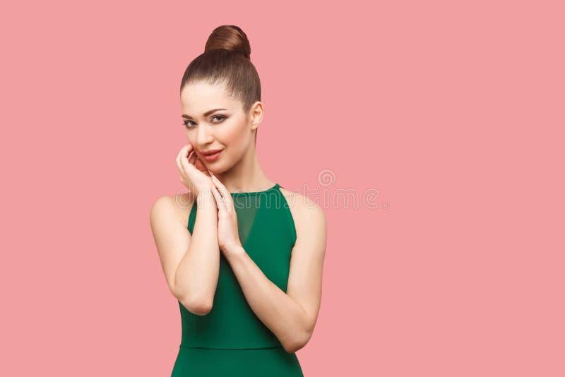 愉快的美丽的年轻女人秀丽画象有小圆面包发型和构成的在接触她的面孔的绿色礼服身分,看 库存图片