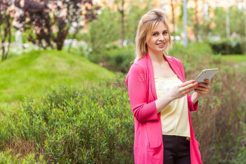 愉快的美丽的年轻成功的博客作者女实业家画象站立在绿色公园的高雅样式的,拿着片剂与 免版税库存照片
