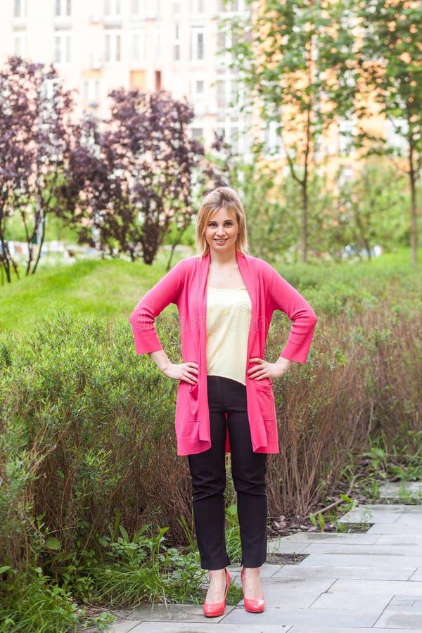 愉快的美丽的年轻成功的女实业家全长画象站立在绿色公园的高雅样式的,握手  免版税库存图片