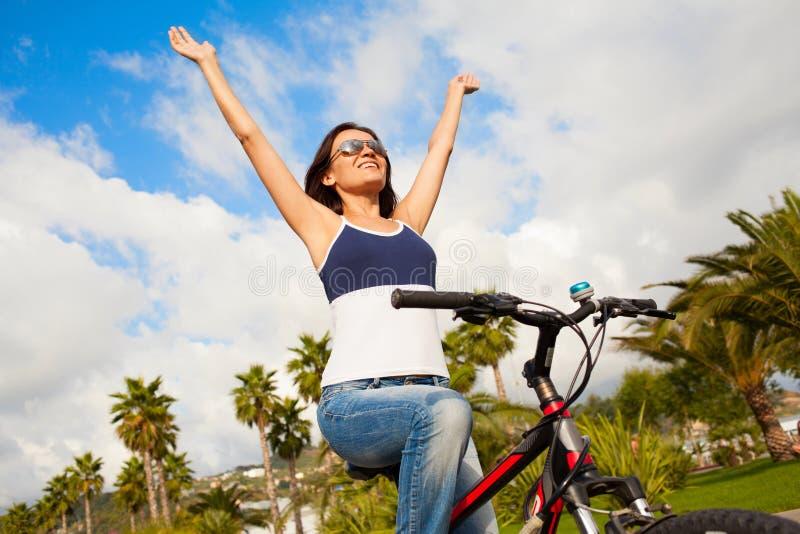 愉快的美丽的性感的女孩妇女骑马自行车用被举的手 免版税图库摄影