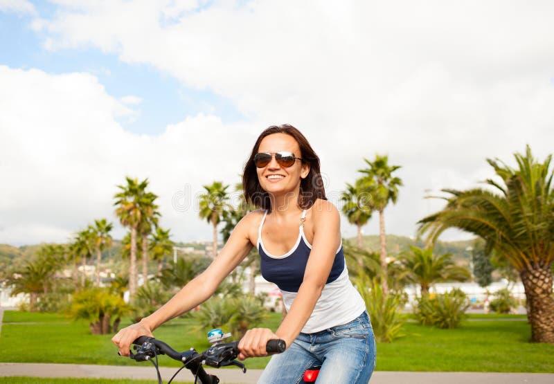 愉快的美丽的性感的女孩妇女骑马自行车 库存照片