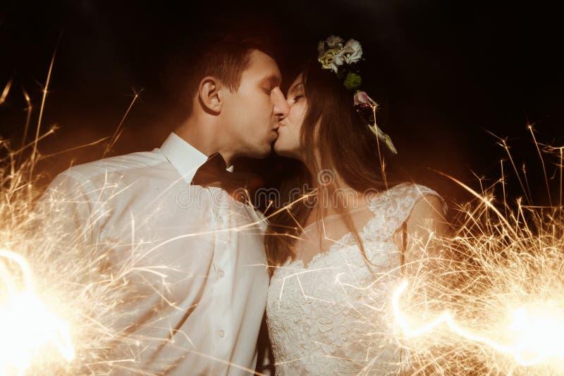 愉快的美丽的拿着烟花的新娘和典雅的时髦的新郎 免版税库存照片